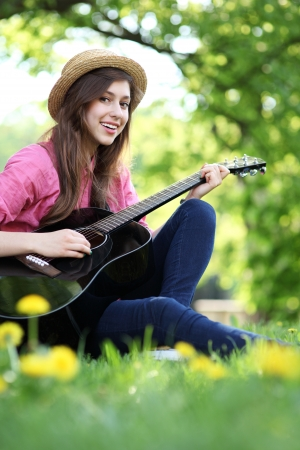 Woman playing guitar in park photo