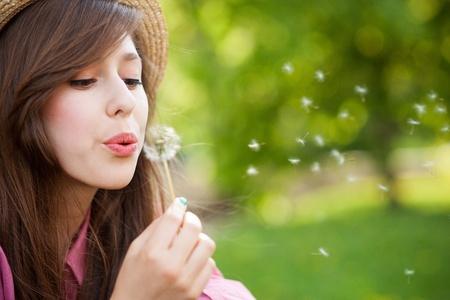 blowing dandelion: Donna soffiando dente di leone