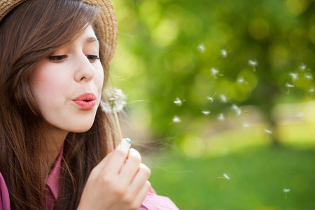Woman blowing dandelion photo
