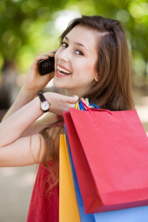 Girl with mobile phone and shopping bags photo