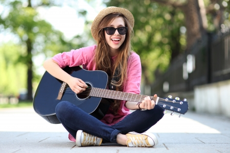 teens playing: Female with guitar Stock Photo