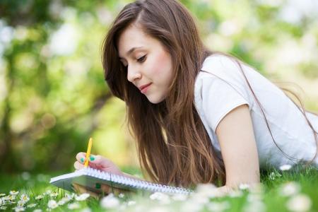 learning by doing: Girl lying on grass with workbook and pencil