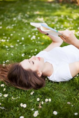 mujer leyendo libro: Mujer acostada en la hierba con un libro