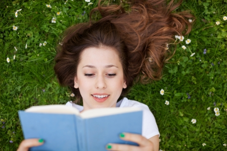 Woman lying down on grass with book photo
