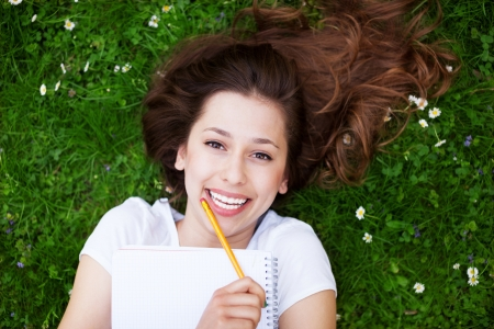 workbook: Young woman outdoors with workbook and pencil Stock Photo