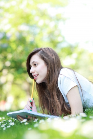 Girl lying on grass with workbook photo