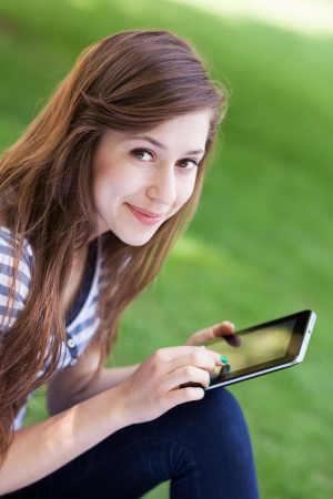 Woman using digital tablet outdoors photo