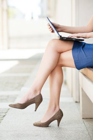 Businesswoman legs with laptop photo
