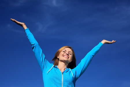 Woman with arms outstretched against blue sky Stock Photo - 14105887