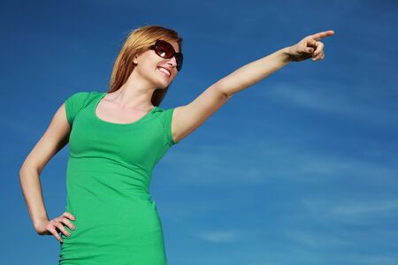 Woman pointing against blue sky