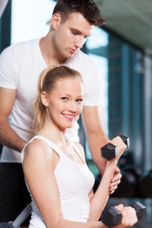 man working out: Woman exercising with personal trainer