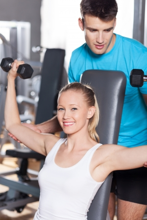 Woman Lifting Weights with Personal Trainer Stock Photo - 14336780