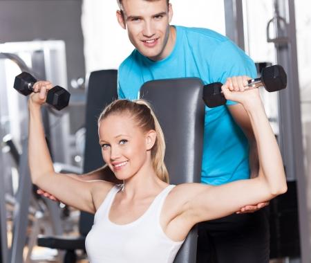 lifting weights: Mujer Levantando Pesas con Personal Trainer Foto de archivo