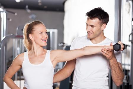 Vrouw Tillen Gewichten met Personal Trainer