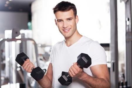 uomo palestra: L'uomo esercita con dumbbells