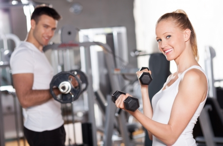 woman lifting weights: Couple in gym exercising with dumbbells Stock Photo