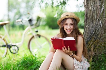 mujer leyendo libro: Mujer joven leyendo al aire libre, libro