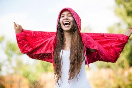 lloviendo: La mujer en gabardina disfrutando de la lluvia
