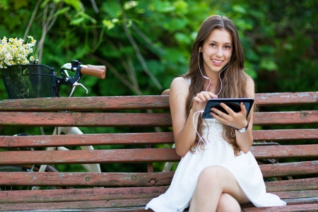 Woman sitting on bench with digital tablet photo