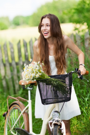Woman with bike by wooden fence Stock Photo - 14430783