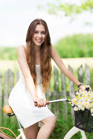 Woman with bike by wooden fence photo
