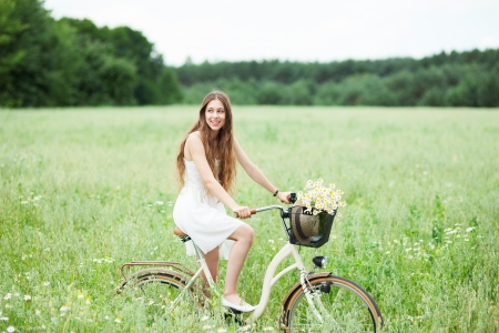 Woman on bicycle in field photo