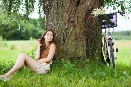 under tree: Woman relaxing under a tree next to a bicycle