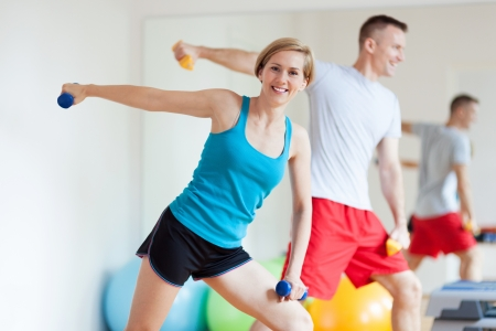 woman lifting weights: Couple working out with dumbbells