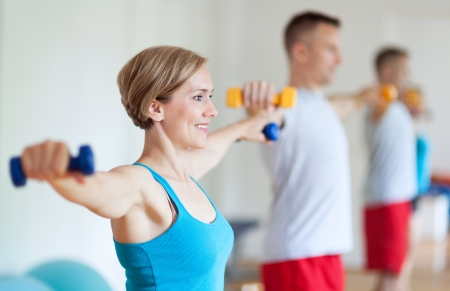 Couple in gym exercising with dumbbells photo
