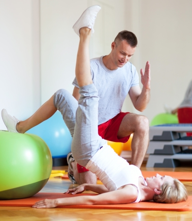 personal training: Woman working out while instructor assisting her Stock Photo