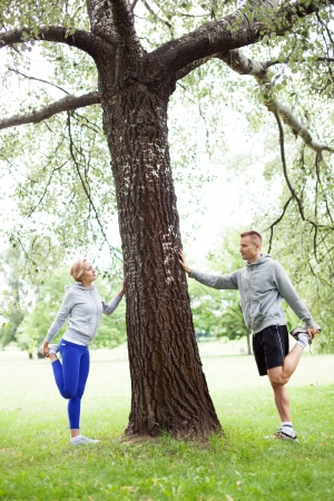 Couple doing stretching exercises in park photo