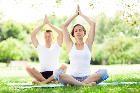 Couple practicing yoga in the park photo