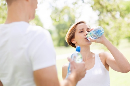standing water: Woman drinking water after exercise