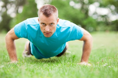 man working out: Man doing press ups outdoors