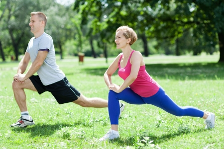 man working out: Man and woman doing stretching exercises Stock Photo