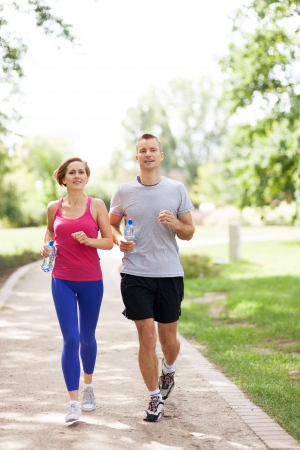 hacer footing: Couple jogging en el parque