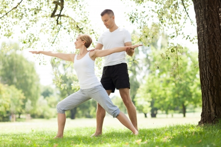 couple exercising: Couple practicing yoga in the park