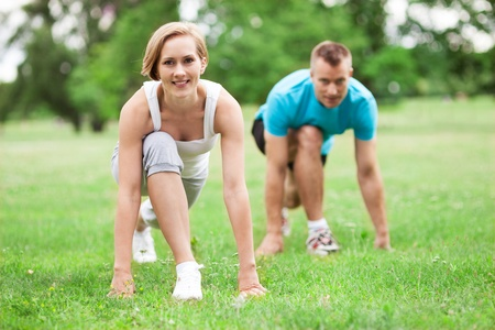 couple exercising: Couple working out in park