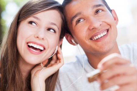 young couple smiling: Young couple listening music together