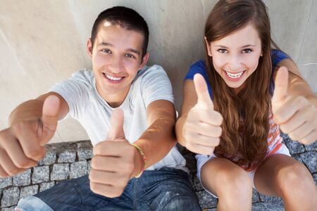 teenage girl happy: Teenage couple with thumbs up  Stock Photo