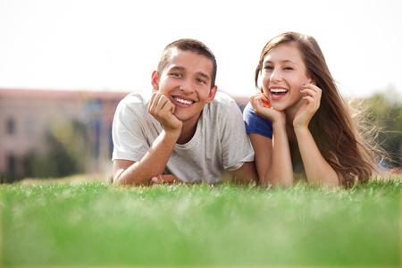 pareja de adolescentes: Pareja joven tumbado en la hierba Foto de archivo