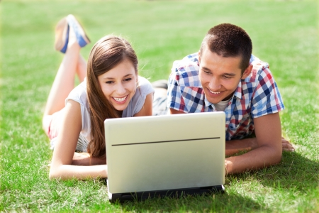 Couple using laptop outdoors photo