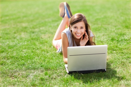 lying on grass: Girl lying on grass with laptop