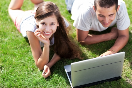 Young couple lying on grass with laptop photo
