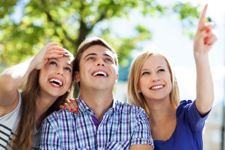happy teenager: Three young friends pointing Stock Photo