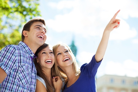 teenagers laughing: Three young friends pointing Stock Photo