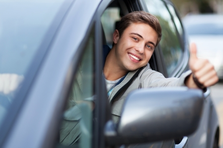 car driver: Young man doing thumps-up in car Stock Photo
