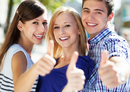thumbs up group: Three young people with thumbs up