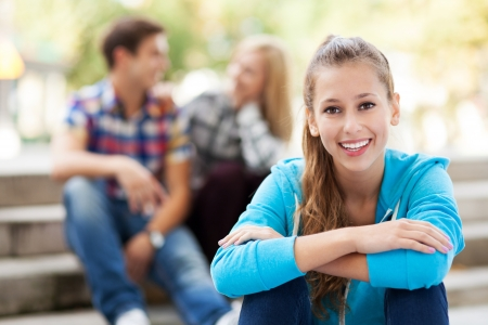 teenagers laughing: Smiling woman with friends in background