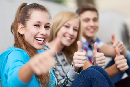 young female: Young people showing thumbs up